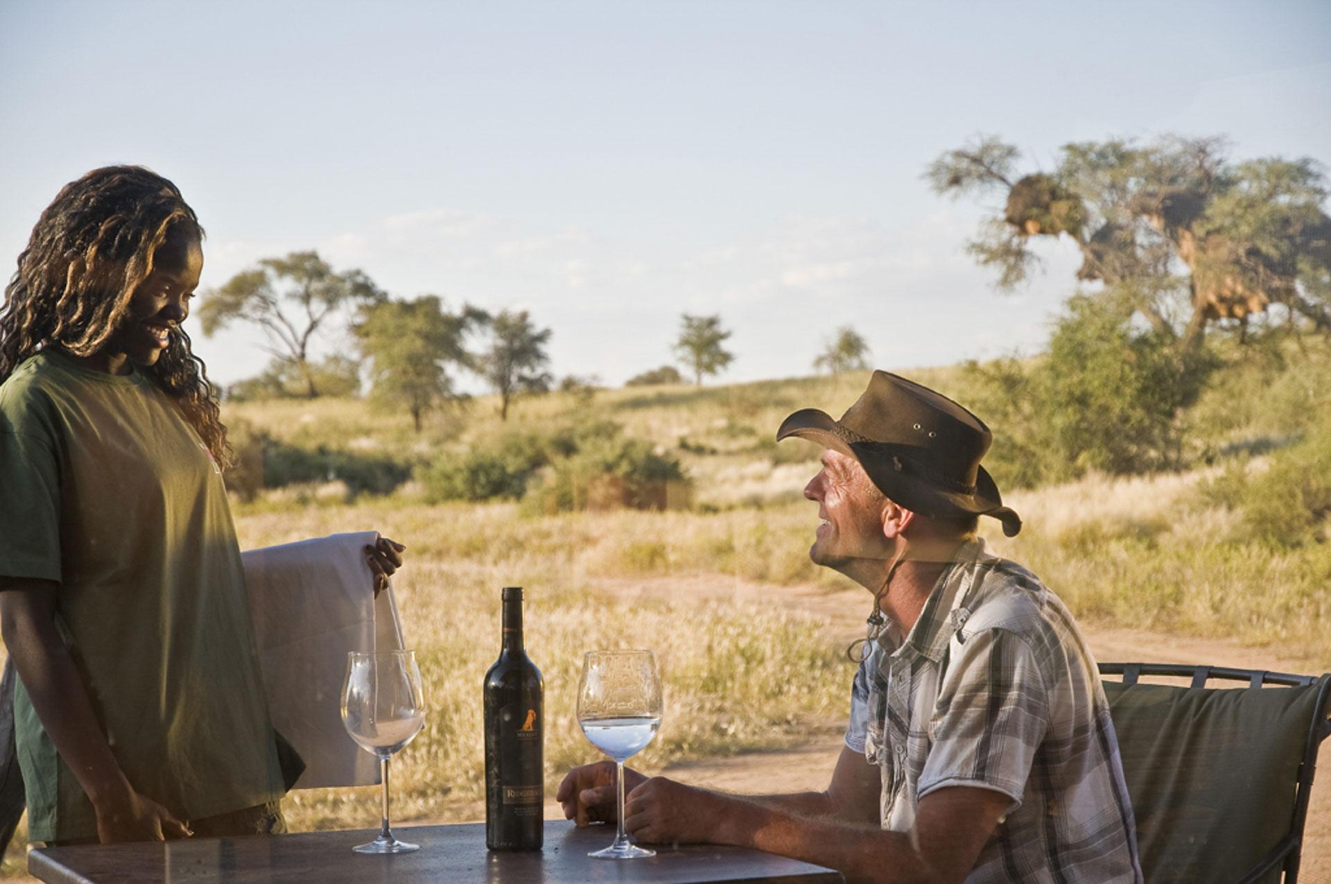 Ein Gast und eine Mitarbeiterin auf der Kalahari Red Dunes Lodge in Namibia